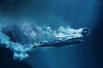 professional swimmer underwater in abyss isolated on blue backgr